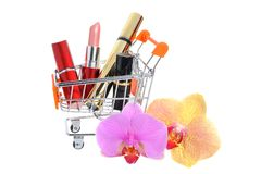Makeup in pushcart with orchid flowers on white Stock Photos