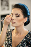 Makeup session with beautiful young brunette woman. Makeup artist doing the eyebrows of an attractive dark hair lady Stock Photo