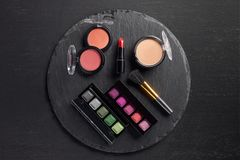 Makeup set with eye shadows and lipstick on round stock photos