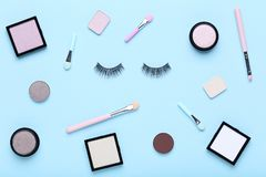 Makeup shadows with brush. And eyelashes on mint background royalty free stock photo