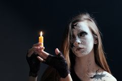 Makeup in the style of Halloween. A young girl with long hair with cracks painted on her face is holding a burning candle. Dark ba royalty free stock images