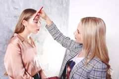 Makeup styling process with pro visagiste and model. Makeup applying process by professional artist wearing fashionable checkered oversized blazer jacket stock images