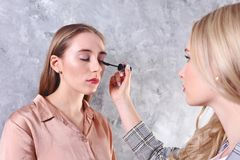 Makeup styling process with pro visagiste and model. Makeup applying process by professional artist wearing fashionable checkered oversized blazer jacket royalty free stock photo