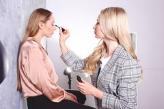 Makeup styling process with pro visagiste and model. Makeup applying process by professional artist wearing fashionable checkered oversized blazer jacket royalty free stock images