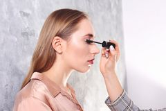 Makeup styling process with pro visagiste and model. Makeup applying process by professional artist wearing fashionable checkered oversized blazer jacket royalty free stock image