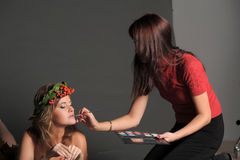 Makeup stylist adjusts the model Royalty Free Stock Image
