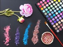 Makeup tools and accessories isolated on black background. Top view and mock up. eye shadows, make up brushes and decorative flowe Royalty Free Stock Image