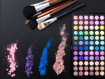 Makeup tools and accessories isolated on black background. Top view and mock up. Lipstick, eye shadows, make up brushes. Royalty Free Stock Photo
