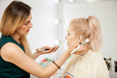 Makeup trainer with a brush applying blush with a brush on model. Applying make up to a young beautiful model Royalty Free Stock Image