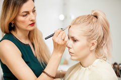 Makeup trainer with a brush applying blush with a brush on model. Applying make up to a young beautiful model Stock Photo