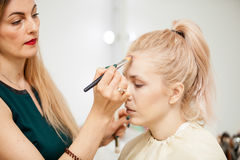 Makeup trainer with a brush applying blush with a brush on model. Applying make up to a young beautiful model Royalty Free Stock Photos