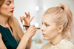 Makeup trainer with a brush applying blush with a brush on model. Applying make up to a young beautiful model Royalty Free Stock Images