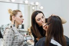 Makeup tutorial course. Makeup teacher with her student girl. Makeup tutorial course at beauty school. Visagiste applying makeup on the eyes. Makeup master class royalty free stock image