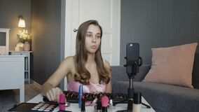 Makeup vlogger influencer creating cosmetic product explainer video. Young woman is filming a new episode for her