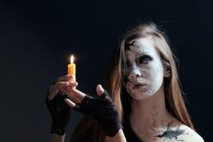 Makeup w stylu Halloween Młoda dziewczyna z długie włosy z pęknięciami malującymi na jej twarzy trzyma płonącą świeczkę Ciemni pó obrazy royalty free