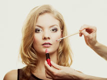 Makeup. Woman applying red lipstick with brush Royalty Free Stock Photography
