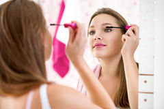 Makeup woman putting lipstick wearing hair rollers getting ready Royalty Free Stock Photos