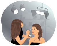 Makeup. Young beautiful woman applying makeup by makeup artist in the studio. Fashion and cosmetic Royalty Free Stock Photography