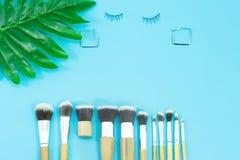 Makeupborstar och örhänge, dagliga sminkhjälpmedel på blått royaltyfria foton