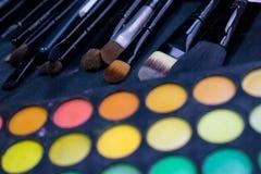 Makeupborstar och färgrik ögonskuggapalett Arkivfoto