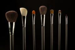 Makeupborstar på en svart bakgrund arkivbild