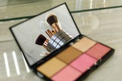 Makeupborstar reflekteras i en palettspegel med skuggor arkivbild