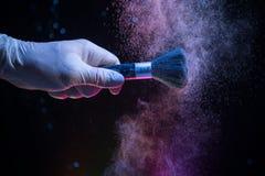 Makeupborste i hand med kosmetiskt pulver på mörk bakgrund med ljus och rök Pudra färgstänk på mörker arkivfoto