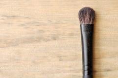 Makeupborste på den Wood tabellen Royaltyfri Bild