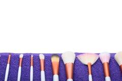 Makeupborsteuppsättning på den purpurfärgade handduken royaltyfri bild