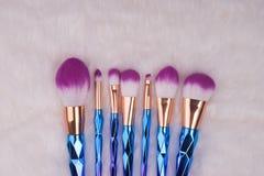 Makeupborsteuppsättning på vit pälsbakgrund Arkivfoto