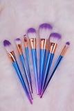 Makeupborsteuppsättning på vit pälsbakgrund Royaltyfria Bilder