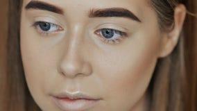 Makeupframsida Flickasminkkonstnären behandlar framsidapulver stock video