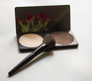 Makeuphjälpmedel som korrigerar pulver och borsten på vit bakgrund Royaltyfri Fotografi
