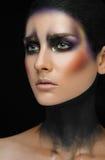 Makeupkonst och härligt modelltema: den härliga flickan med idérik sminksvart-och-lilor och guld färgar på en svart backgroun arkivbilder