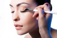 Makeupkonstnär som använder borsten för att applicera ögonskugga på framsida av kvinnan royaltyfria foton