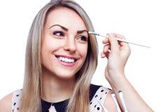 Makeupkonstnär som applicerar ögonskugga på framsidan av kvinnan som isoleras på vit fotografering för bildbyråer
