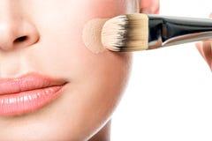 Makeupkonstnär som applicerar det vätsketonala fundamentet på framsidan royaltyfri bild