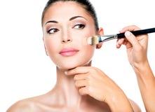 Makeupkonstnär som applicerar det vätsketonala fundamentet på framsidan royaltyfria bilder
