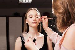 Makeupkonstnär som applicerar en abc-bok på en ögonlock av en klient Fotografering för Bildbyråer
