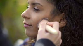 Makeupkonstnär som applicerar pulver med borsten på kinder av den nätta modellen för blandat lopp royaltyfri bild