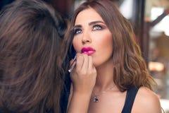 Makeupkonstnär som applicerar smink på härlig modell Arkivfoto