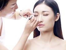 Makeupkonstnär som arbetar på en kvinnlig asiatisk modell fotografering för bildbyråer