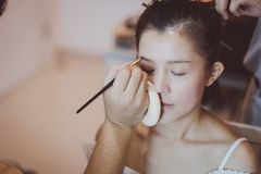 Makeupkonstn?r som arbetar p? h?rlig asiatisk modell arkivbild