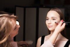 Makeupkonstnär som baddar fundamentet på en hud av en flicka Royaltyfri Bild