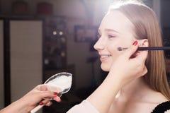 Makeupkonstnär som baddar fundamentet på en hud av en lycklig modell Fotografering för Bildbyråer