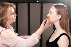 Makeupkonstnär som baddar fundamentet på en hud av en modell Royaltyfria Bilder