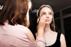 Makeupkonstnär som baddar fundamentet på en kvinna Royaltyfria Bilder