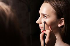 Makeupkonstnär som baddar fundamentet på en modell Royaltyfria Foton