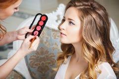 Makeupkonstnär som förbereder bruden för bröllopet i en morgon Royaltyfria Bilder