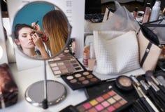 Makeupkonstnär som gör sminket för flicka royaltyfri fotografi